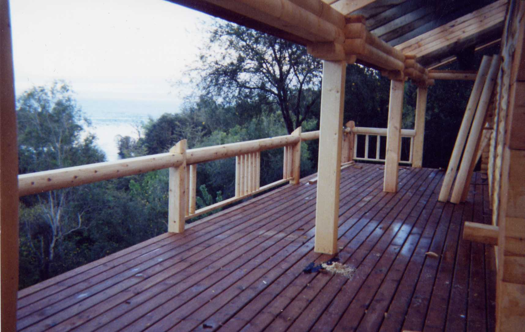 Partly covered front deck w/machined log posts & rails